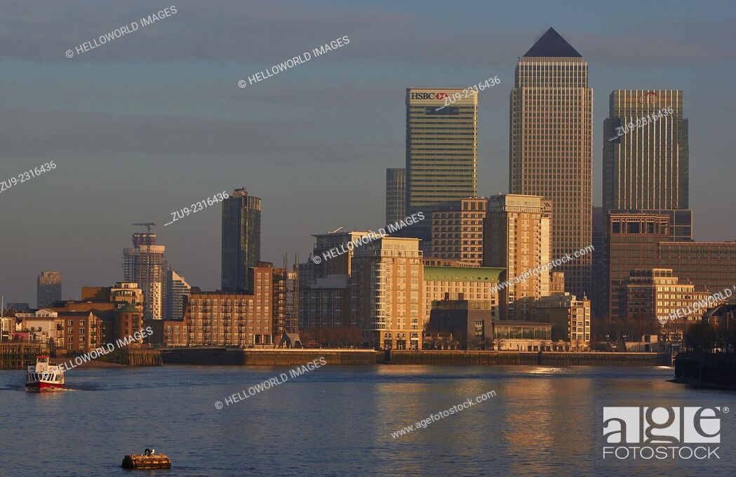 Stock Photo: River cruise boat on the Thames near Canary Wharf at sunset, east London, England, Europe.