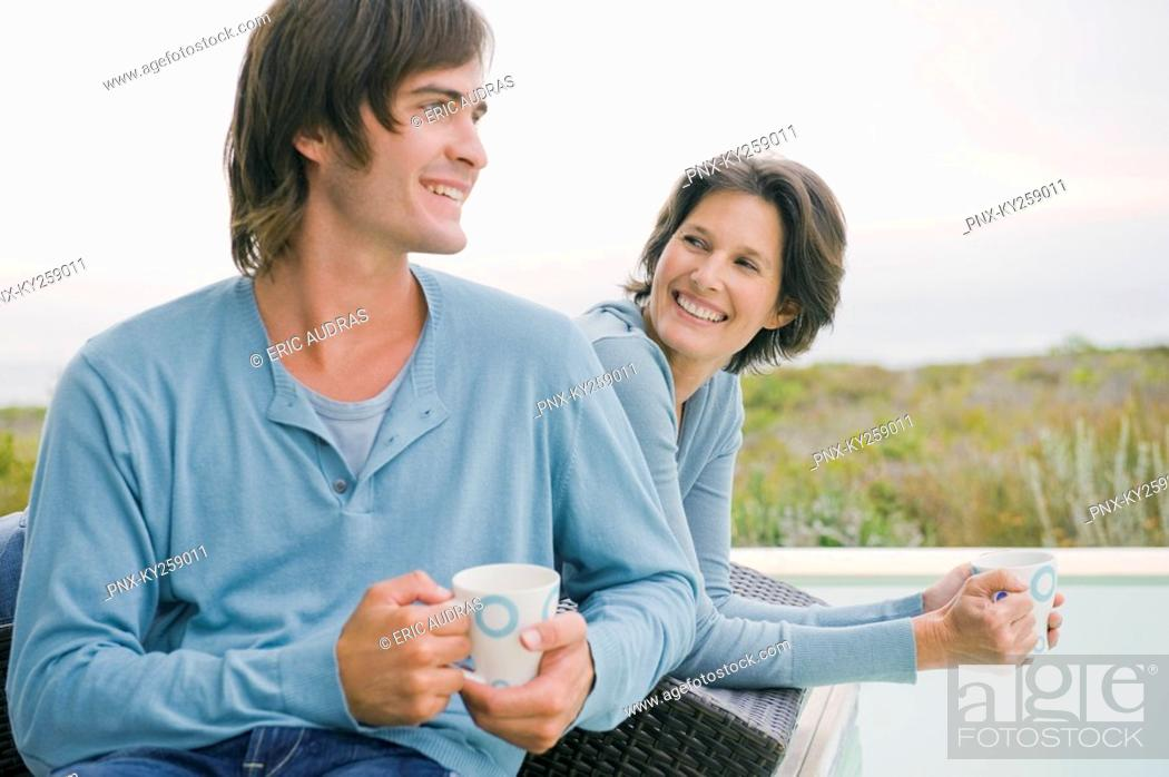 Stock Photo: Woman and her son drinking tea at the poolside.