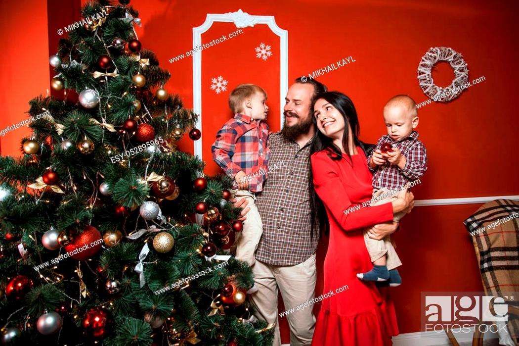 Stock Photo: Christmas family portrait in home holiday living room, kids and baby with parents, decorating house with Xmas tree and gifts.