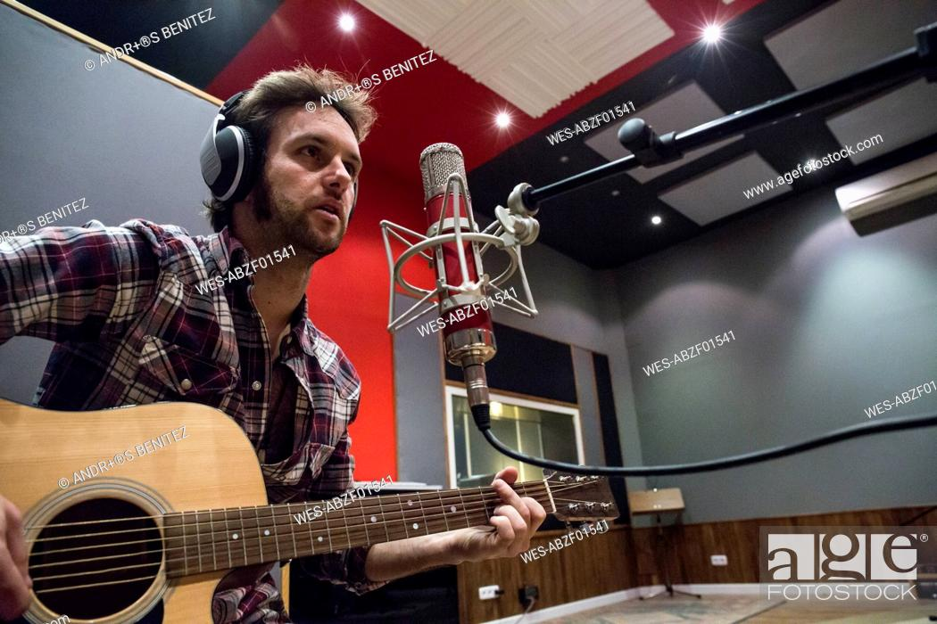 Photo de stock: Man playing guitar in a recording studio during a musical recording.