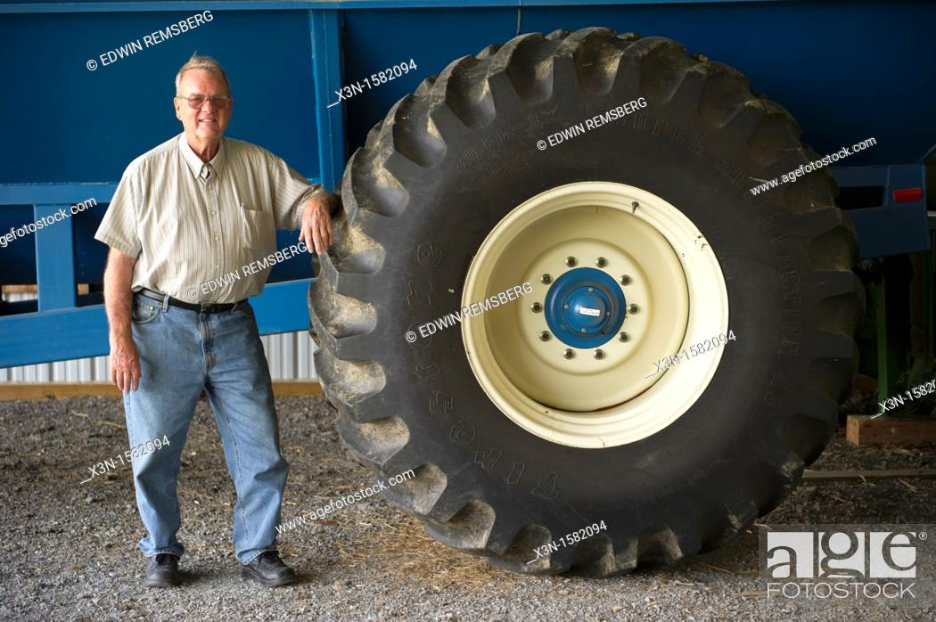 Stock Photo: Grain producer standing by tire of a tractor used for harvesting, Montgomery County Maryland USA.