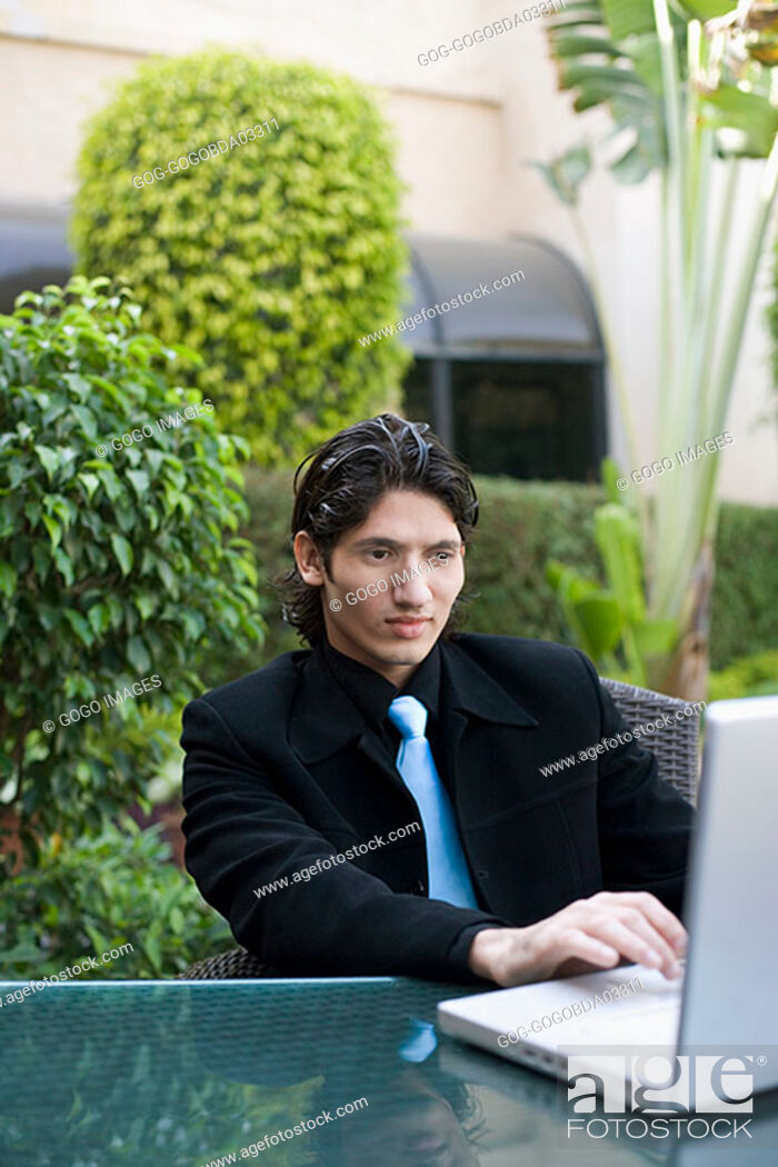 Stock Photo: Businessman using laptop outdoors.