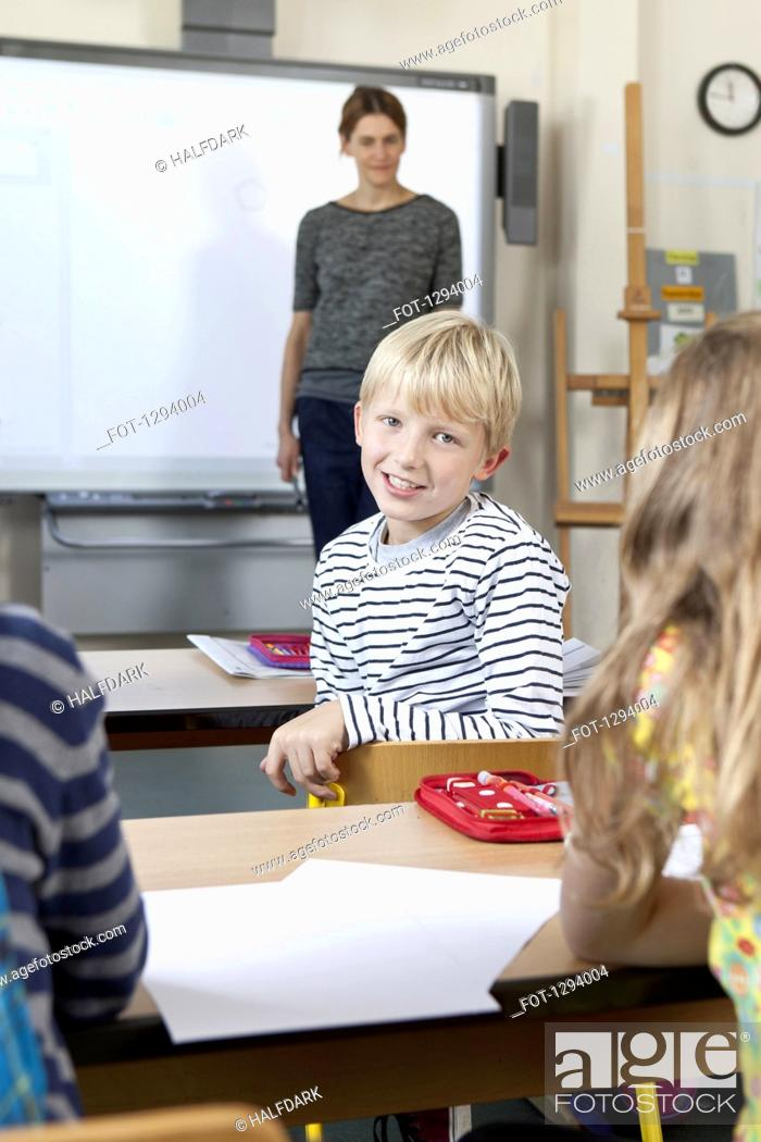 Stock Photo: Boy sitting in classroom, smiling.