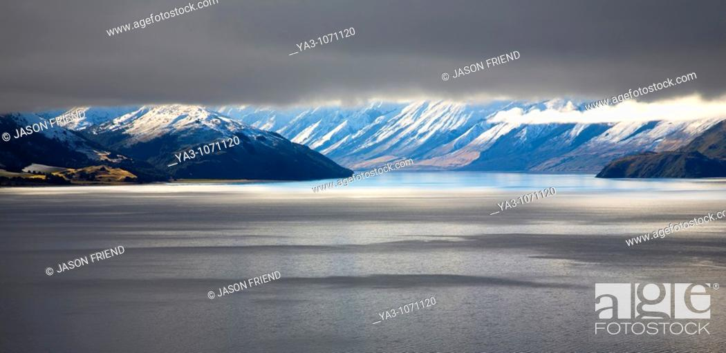 Stock Photo: New Zealand, Otago, Lake Hawea  The Southern Alps revealed through a small gap between dense snow clouds and the surface of Lake Hawea.