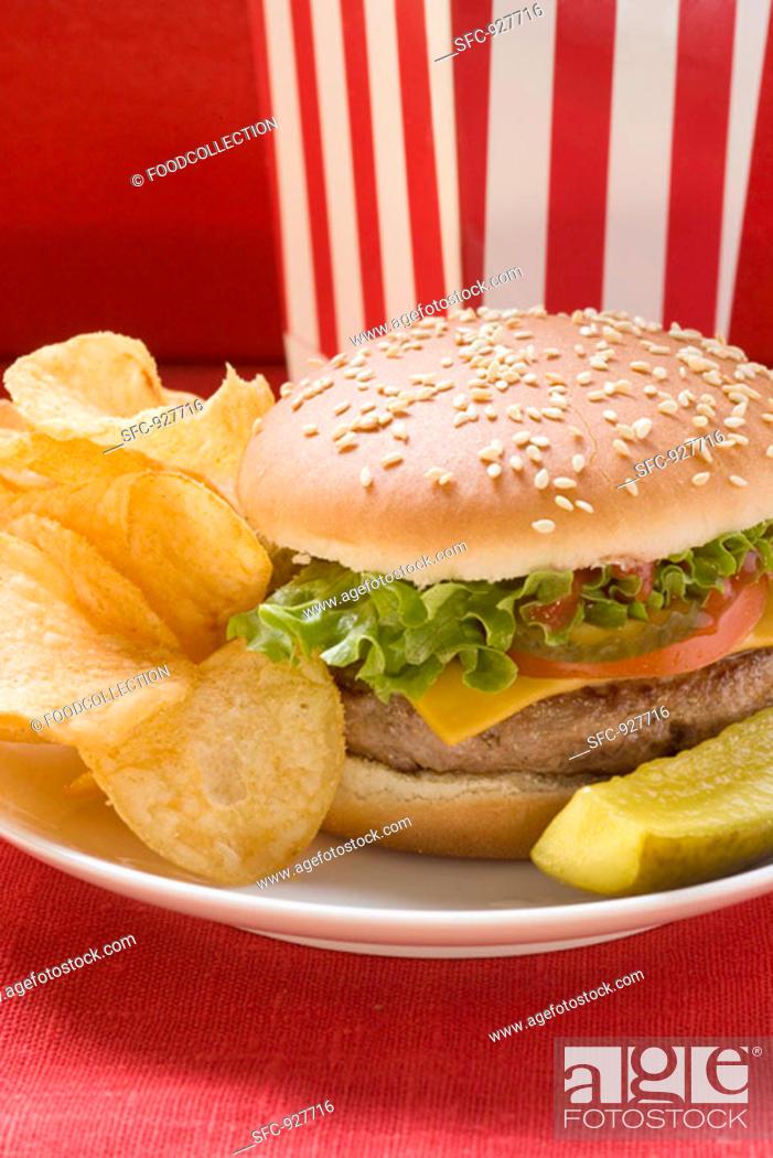 Stock Photo: Cheeseburger with potato crisps and gherkin.