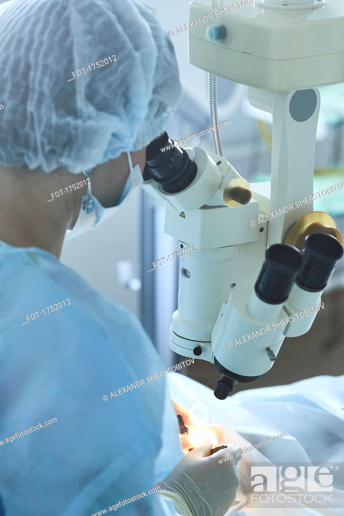 Stock Photo: Surgeon using machinery during eye surgery.