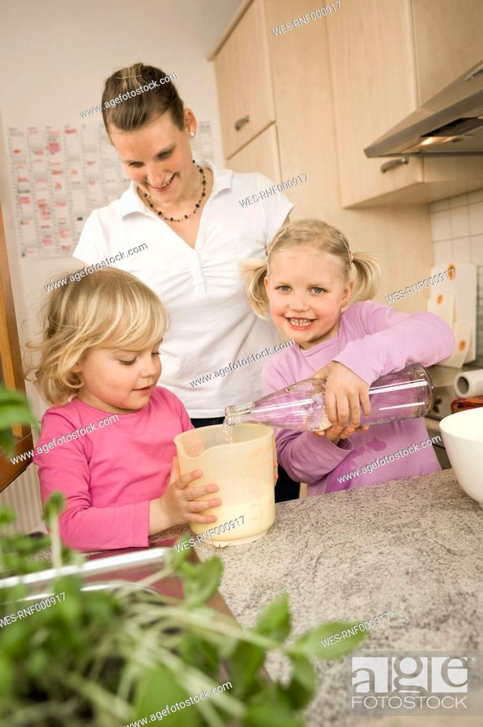 Stock Photo: Mother and daughter pouring water into measuring cup.