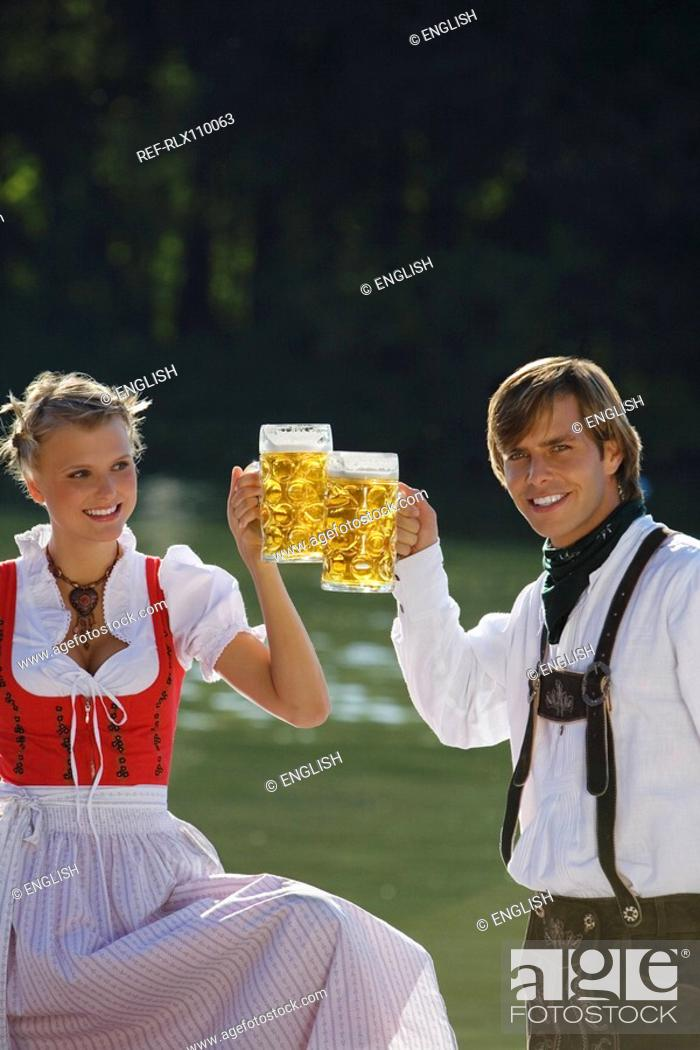 Stock Photo: Young couple in traditional Bavarian outfit, toasting with beer glasses, Munich.