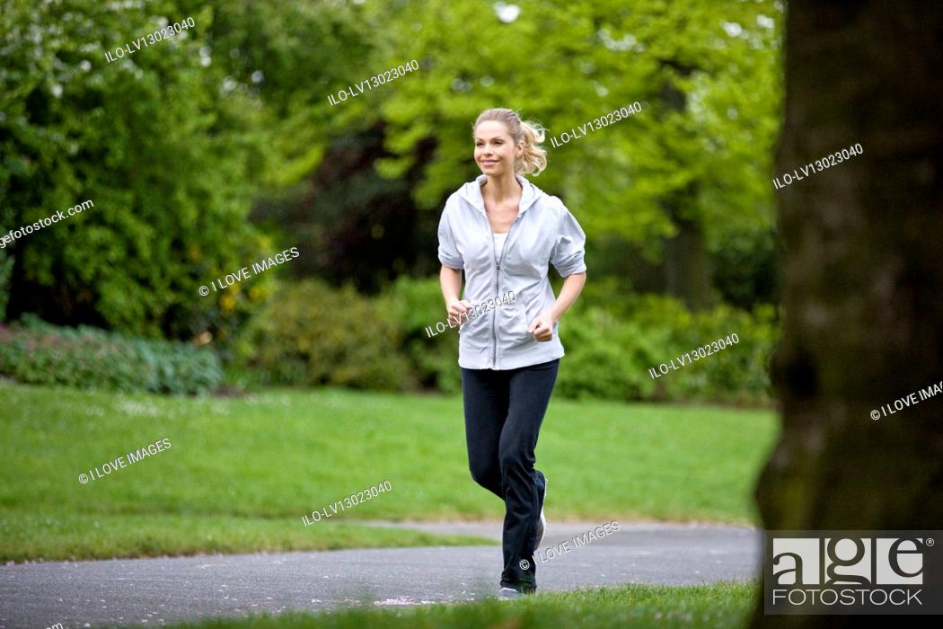 Stock Photo: A mid adult woman jogging in the park.