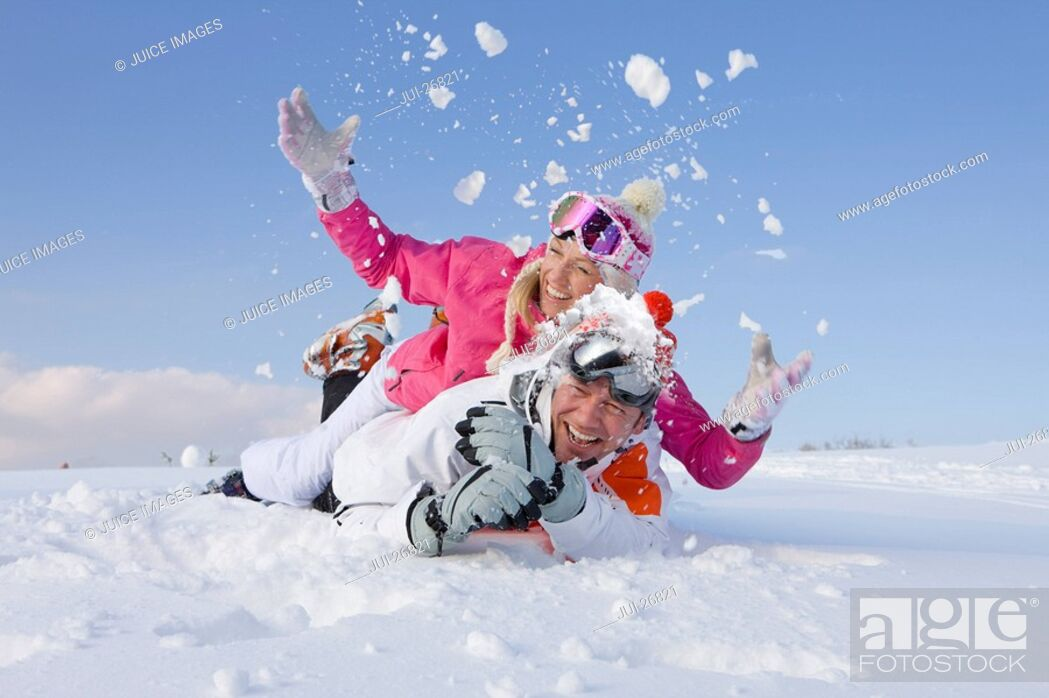 Stock Photo: Couple laying together and throwing snow.