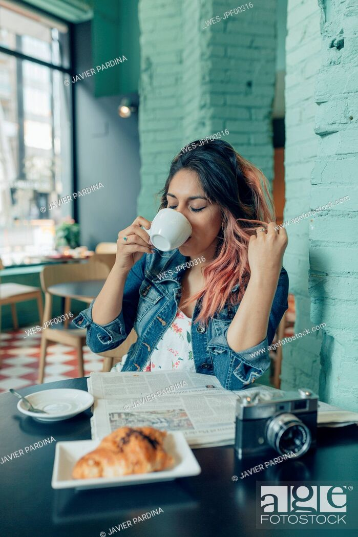 Stock Photo: Woman sitting in coffee shop drinking coffee.