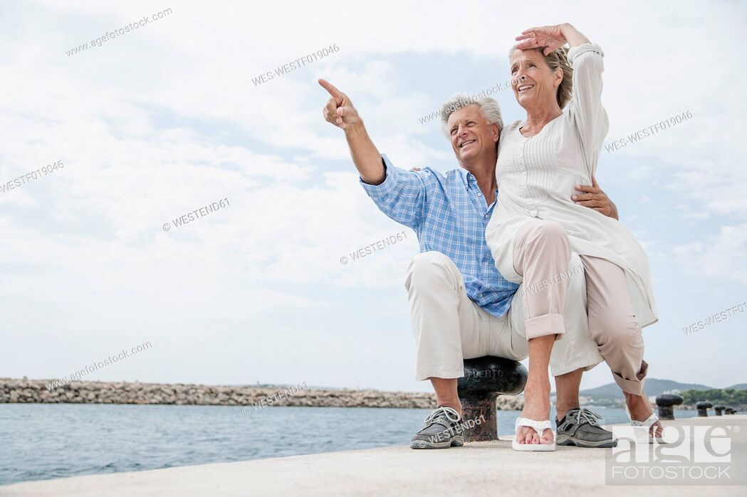Stock Photo: Spain, Senior couple at harbour, smiling.