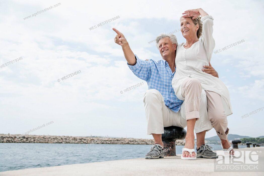 Stock Photo: Spain, Senior couple at harbour, smiling.