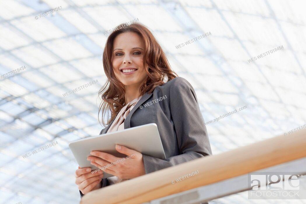 Stock Photo: Germany, Leipzig, Businesswoman using digital tablet, smiling, portrait.