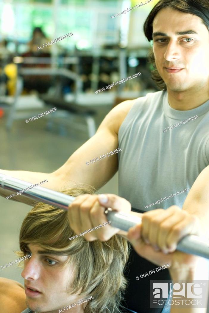 Stock Photo: Man lifting barbell while second man spots.
