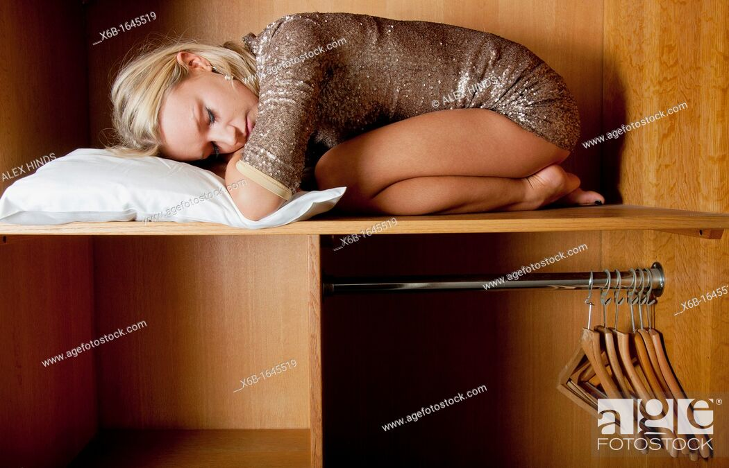 Stock Photo: Young woman, 18-25 years, sleeping in wardrobe space in a hotel room.