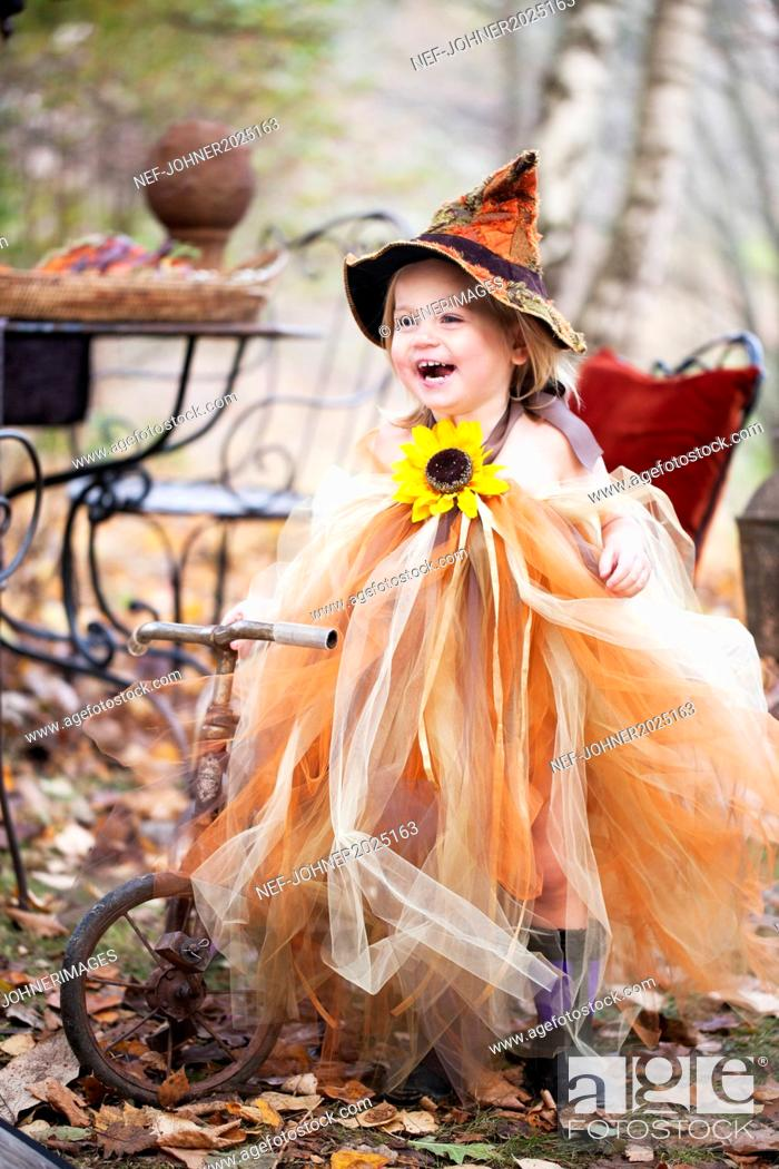 Imagen: Laughing girl wearing witch hat on tricycle.