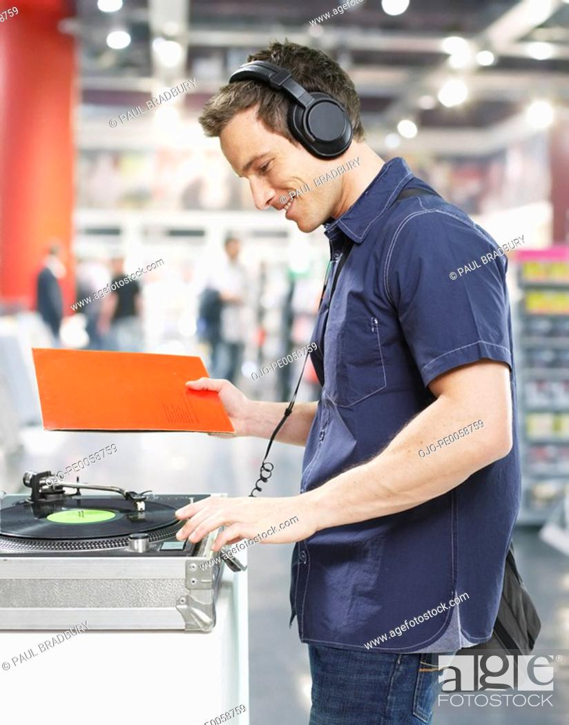 Stock Photo: Man wearing headphones at record player in store.