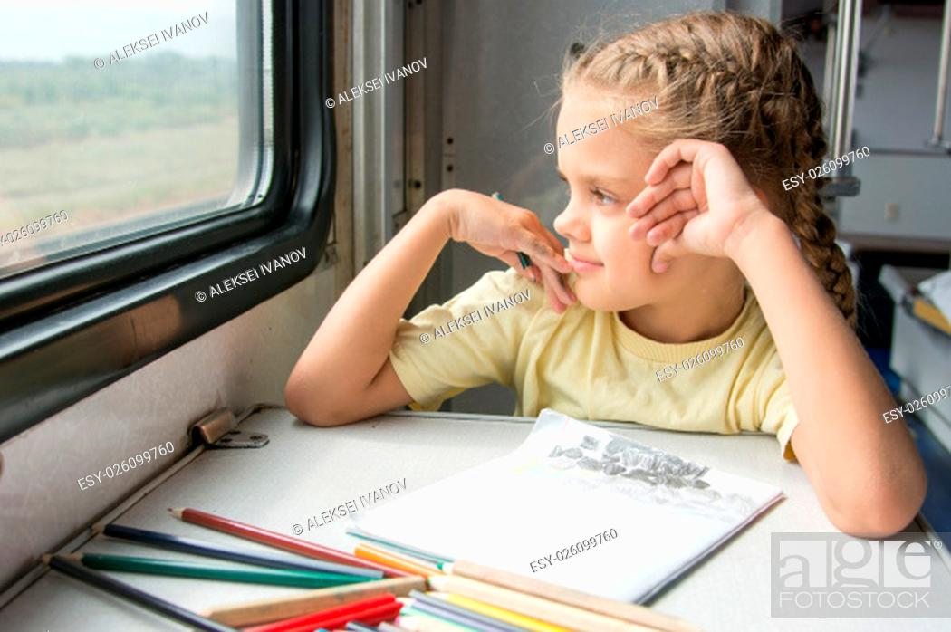 Stock Photo: Six year old girl draws a pencil in a notebook for a side table in the second-class train carriage.
