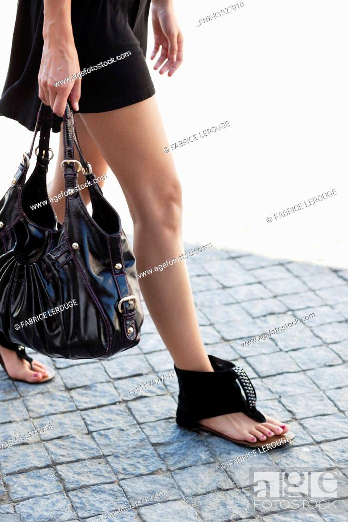 Stock Photo: Low section view of a young woman wearing modern flat sandal and walking.