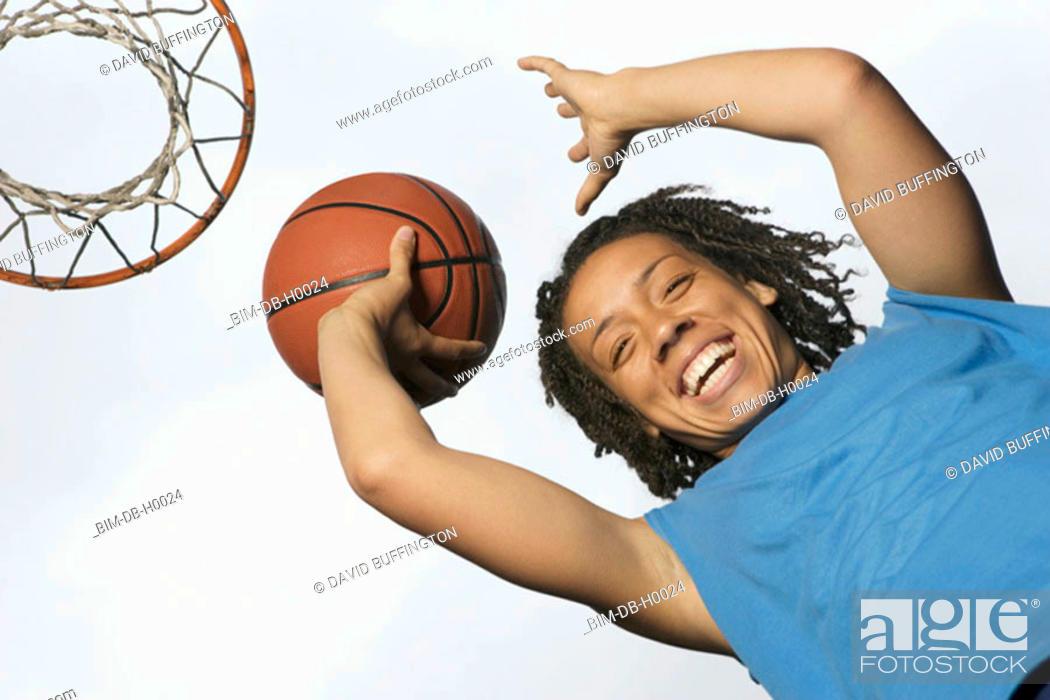 Stock Photo: Low angle portrait of teenage girl shooting hoops.