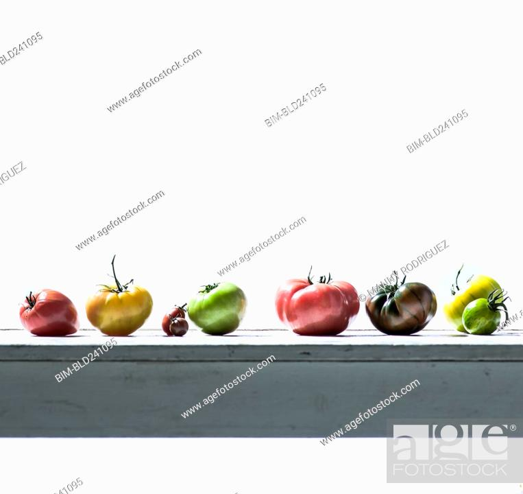 Stock Photo: Row of fresh tomatoes on wooden table.