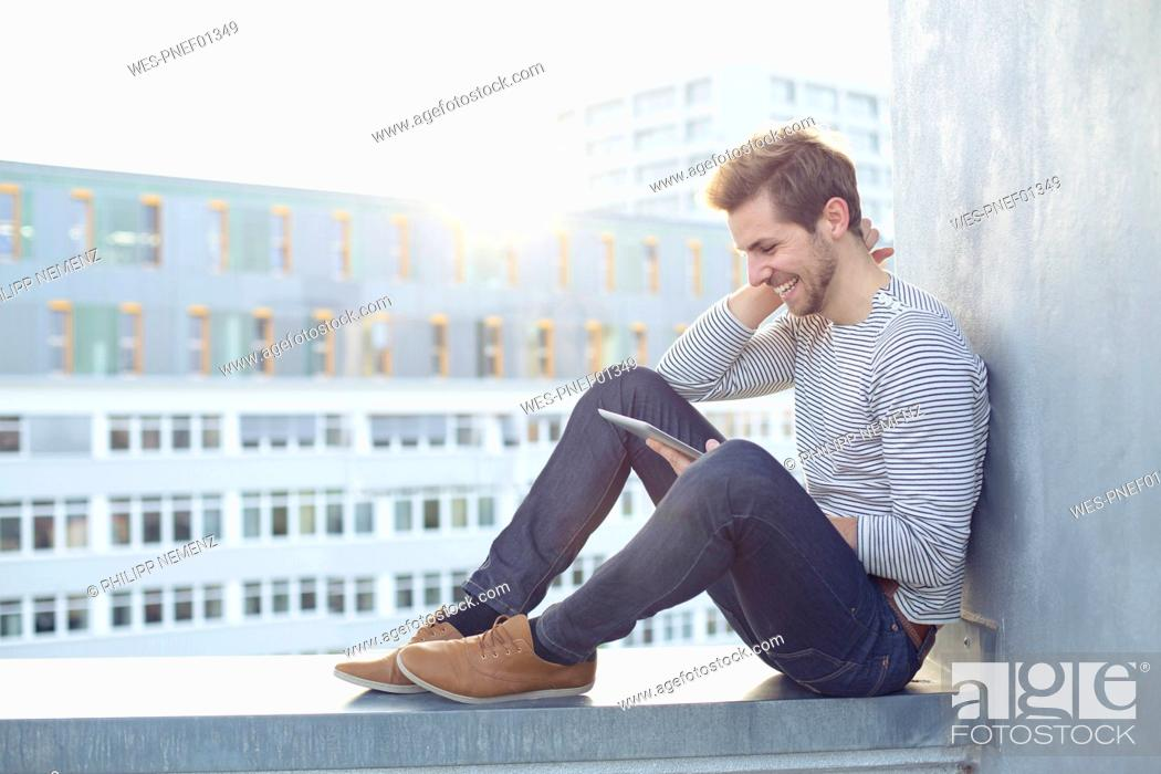 Imagen: Happy young man sitting on a wall using tablet.