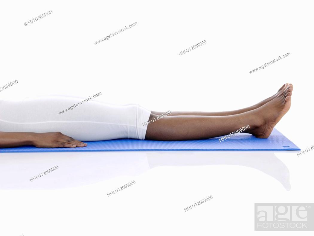 Stock Photo: Young woman lying on exercise mat (low section).