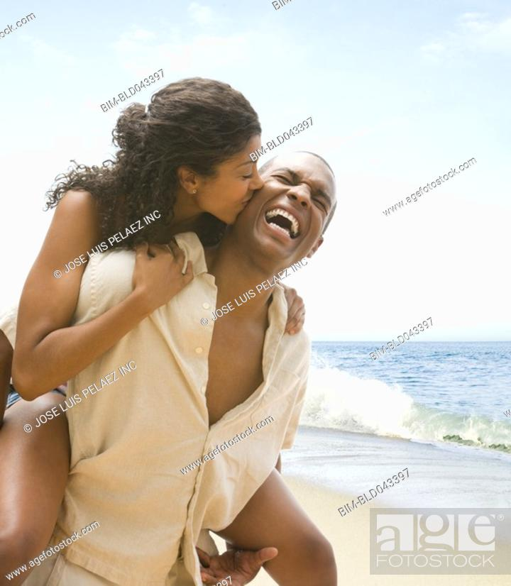 Stock Photo: African American man giving girlfriend piggyback ride.