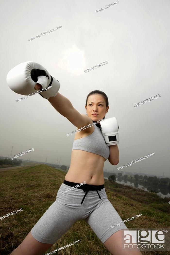 Stock Photo: View of a young woman boxing.