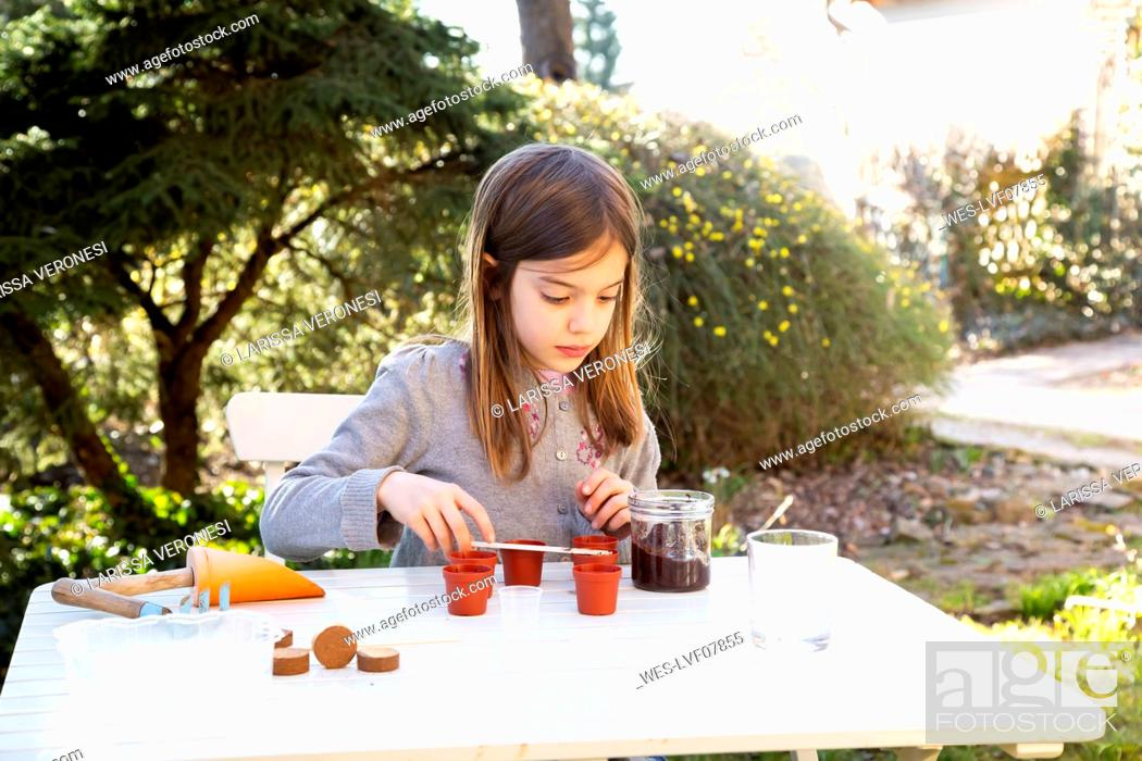 Stock Photo: Portrait of little girl at garden table sowing seeds.