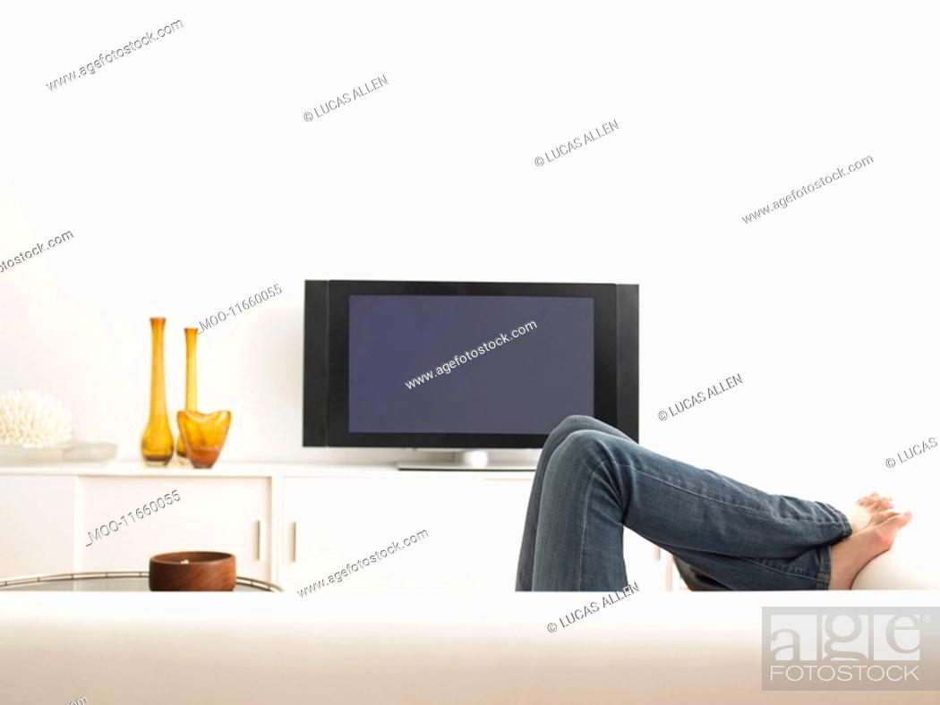 Stock Photo: Woman lying on sofa low section.