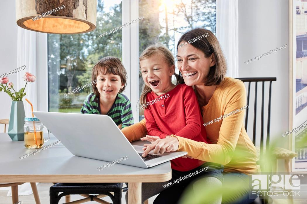 Stock Photo: Happy mother with two children using laptop at home.