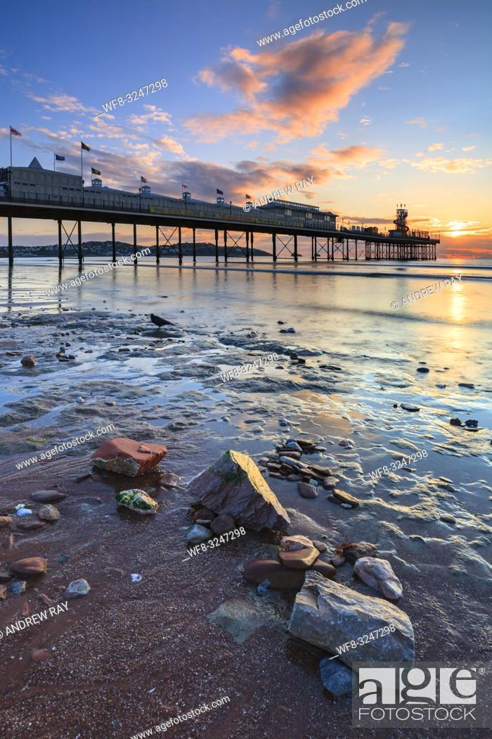 Stock Photo: Rocks on the beach provide the foreground interest in this image featuring Paignton Pier which was captured at sunrise.