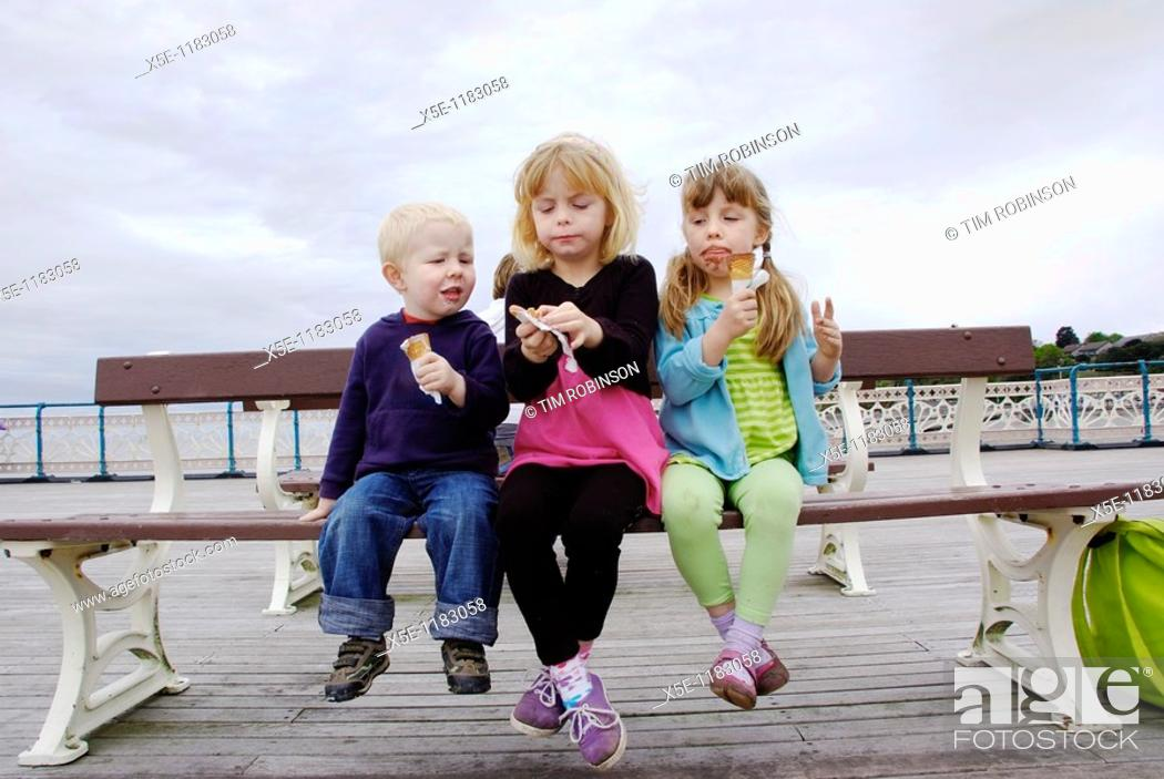 Stock Photo: 3 year boy, 7 year girl and 6 year girl sitting on bench at seaside eating ice creams.