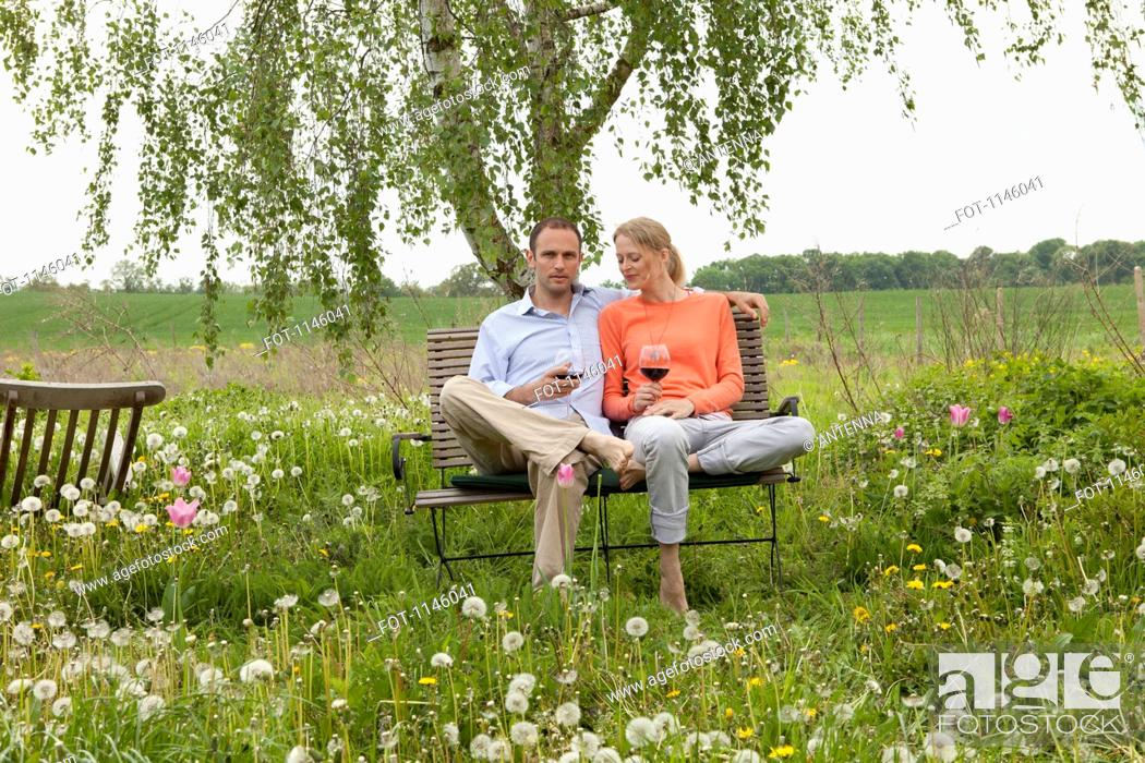 Stock Photo: A couple sitting on a bench in their backyard enjoying a glass of red wine.