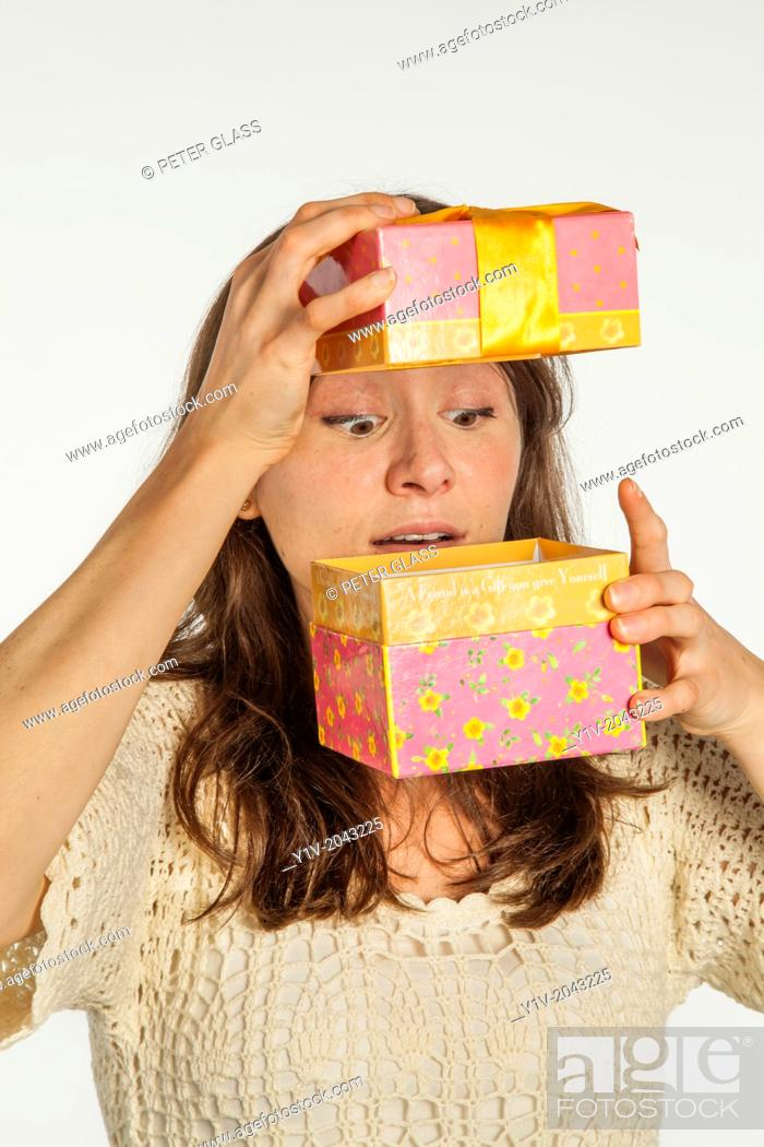 Stock Photo: Young woman holding a gift box.