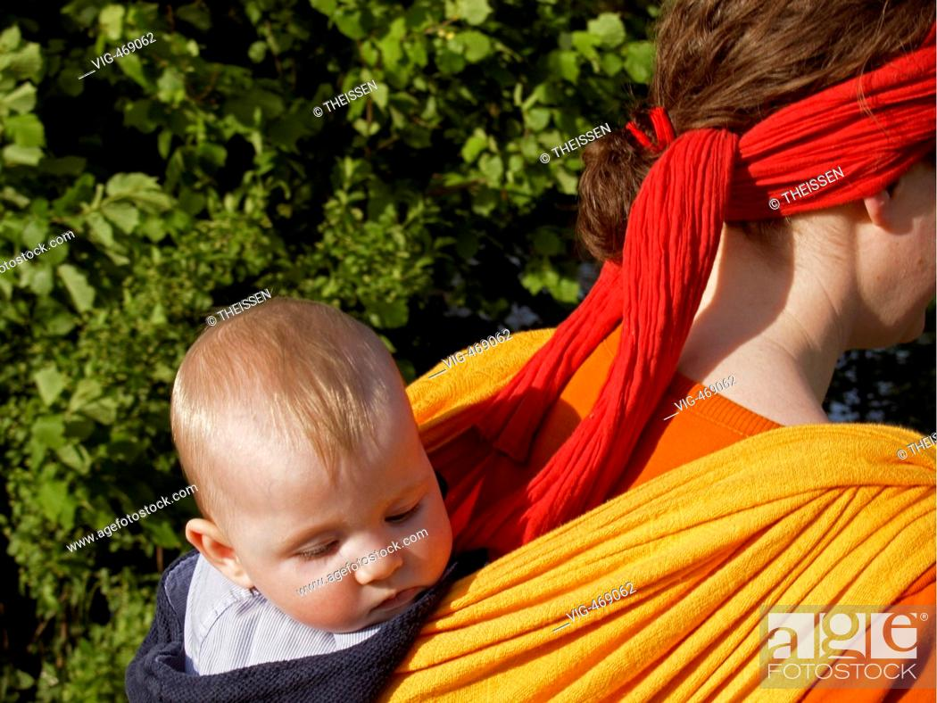 3a3f8c9a274 Stock Photo - young mother carrying her baby in a baby sling on her back  going for a walk in the nature. - 01 01 2007