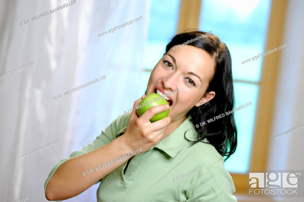 Stock Photo: Woman taking a large bite from a green apple, healthy diet.