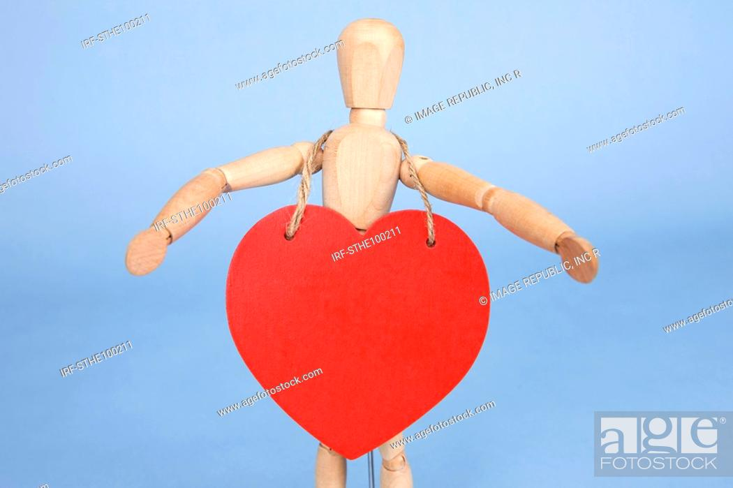 Stock Photo: heart shape hung on the wooden doll.