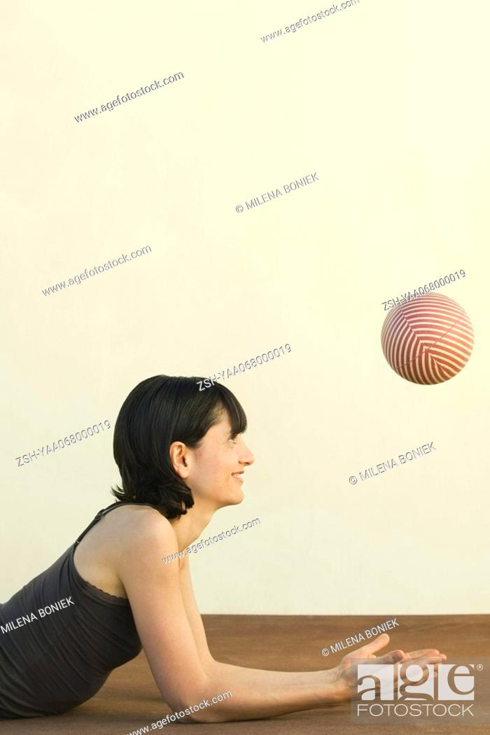 Stock Photo: Woman lying on the ground, catching ball, side view.