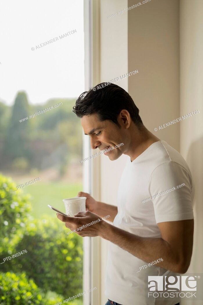 Stock Photo: India, Man at window holding coffee cup and mobile phone.