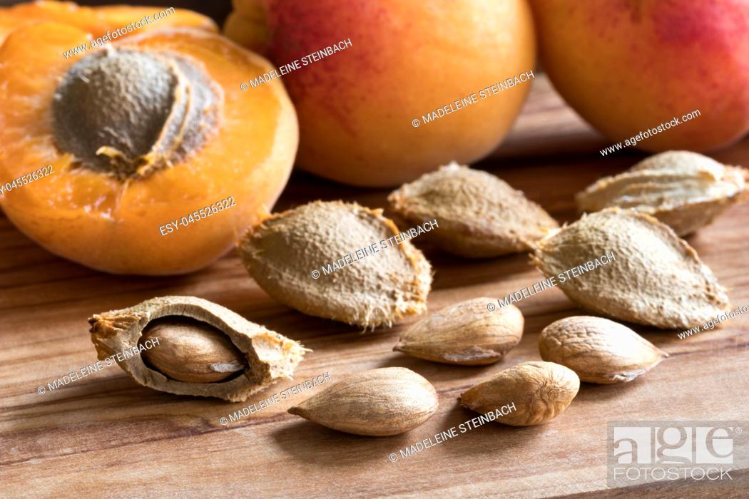 Stock Photo: Apricot kernels and ripe apricots on a wooden background.