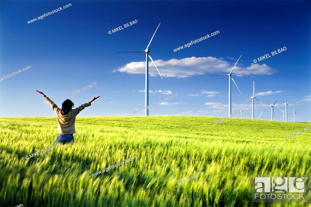 Stock Photo: woman in a windmills field, windfarm.