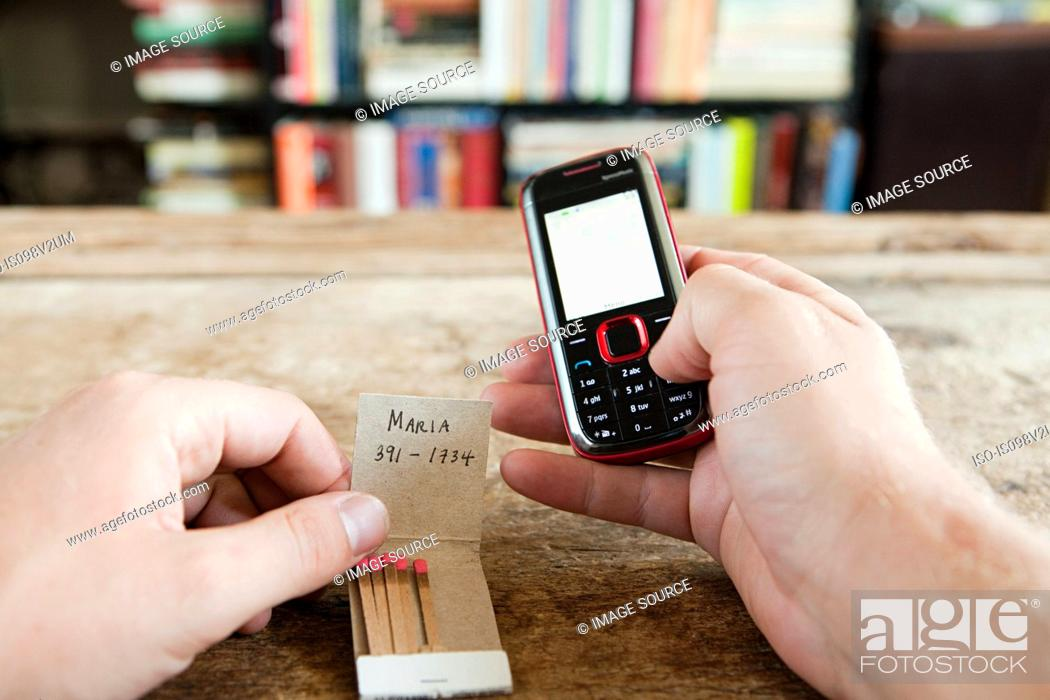 Stock Photo: Person calling number written on matchbook.