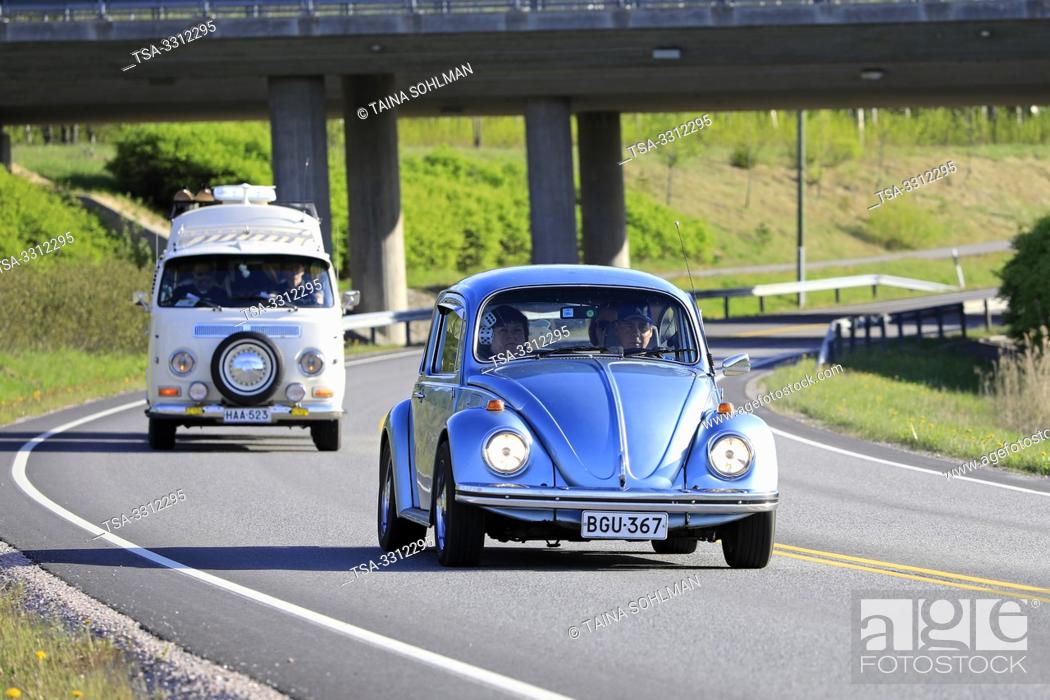 Stock Photo: Salo, Finland. May 18, 2019. Classic 1970s Volkswagen Beetle, or Type 1 and white VW camper van, or Type 2 on road on Salon Maisema Cruising 2019.