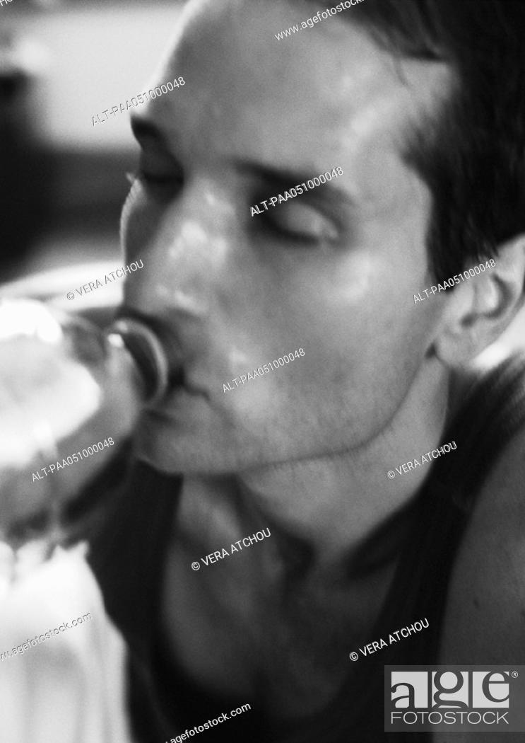 Imagen: Man drinking from bottle, close-up, b&w.