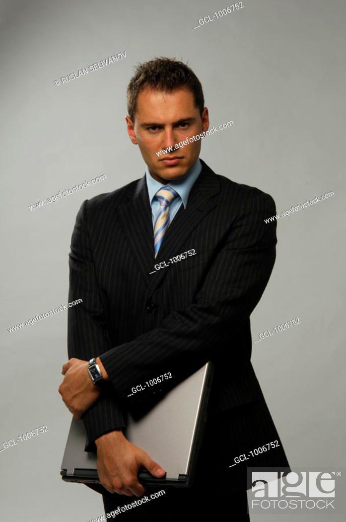 Stock Photo: Portrait of a businessman holding a laptop.