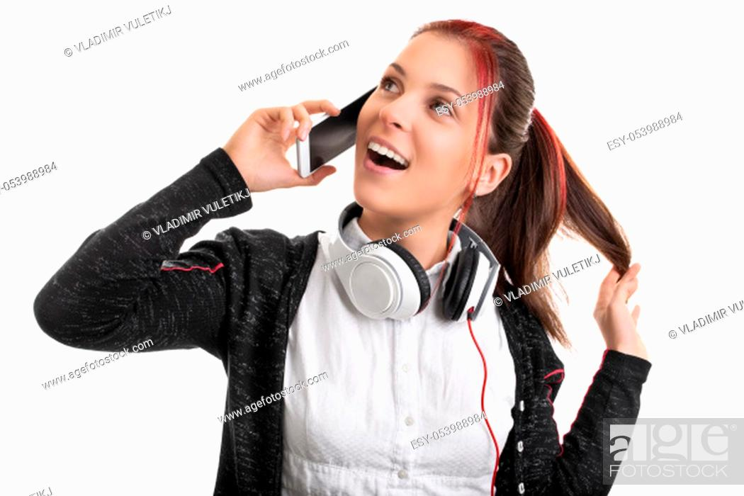 Stock Photo: Close up shot of a beautiful smiling young girl in uniform with headphones around her neck, talking on the phone and playing with her hair.
