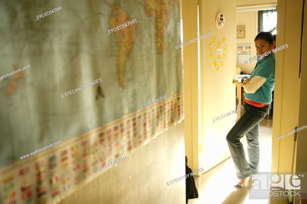 Stock Photo: Teenage girl 15-17 leaning on doorframe.